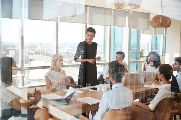 leadership coaching in action - female leader talking to a table of colleagues | Yes Psychology